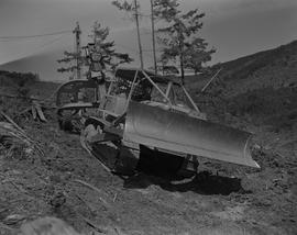Logging, 1967; man sitting in a CAT dozer ; logging debris in background