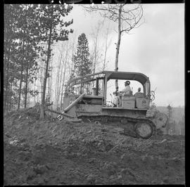 Heavy duty equipment operator, Nanaimo ; side view of a man operating a bulldozer on a hill of dirt