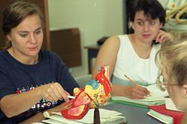 C/Care (students in action), 1993, students with model of a human heart [3 of 3 photographs]