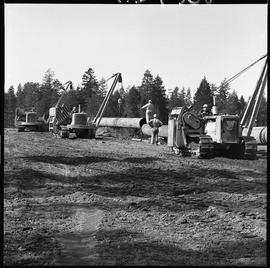 Heavy duty equipment operator, Nanaimo ; man standing on a pipe ; three pipelayers lifting a larg...