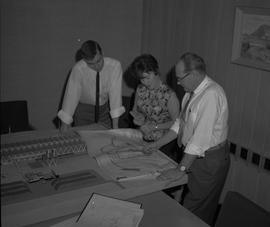 Business Management, 1964; three people looking at blueprints; architectural models on table [1 o...