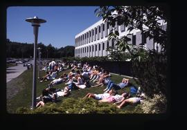 Students on grassy hill enjoying the sun