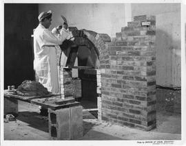 Bricklaying; a student building the arch on a brick fireplace ; Photo by the Division of Visual E...