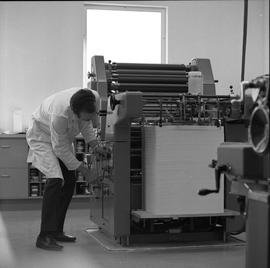 BCVS Graphic arts ; a man adjusting knobs on printing equipment and looking at stacked paper