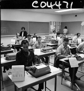 BC Vocational School Commercial Program; students typing; instructor in the background (photograp...