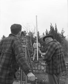 Survey, 1964; three men surveying land above a stone wall in a residential yard [2 of 2]