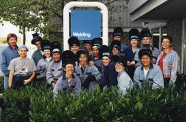 Welding, group shot of students in welding helmets and uniforms standing outside in front of the ...