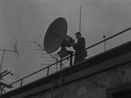 BCIT Broadcast and Television, 1964; man standing next to a satellite dish located on a roof