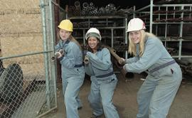 BCIT women in trades; plumbing, students in uniforms and hard hats carrying piping material [1 of...