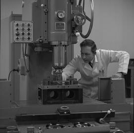 Mechanical technology, 1968; man in a lab coat adjusting settings on a drill