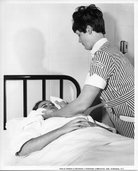 BCVS Practical Nursing student holding something to patient's face, 1967