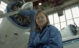 Canadian women at work; woman in uniform in front of an airplane inside a hangar [2 of 3 photogra...