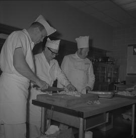 Tow boat cook course; instructor and two students chopping potatoes in a kitchen