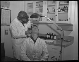 Industrial First Aid, Nanaimo; First Aid Attendant holding a q-tip and checking the left eye of a...