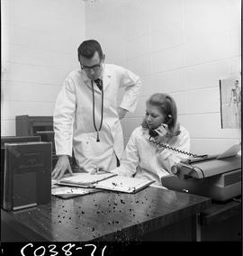 BC Vocational School Commercial Program; medical office with a woman sitting at a desk talking on...