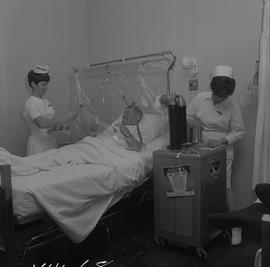 Nursing, 1968; two nurses attending to a patient in a oxygen tent, one nurse passing medication t...