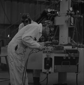 Welding, 1968; man wearing protective goggles welding ; welding equipment in background ; man wor...