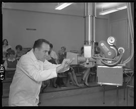 Medical radiography, 1967; man in a lab coat using radiography apparatus ; people sitting at desk...