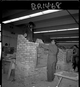 B.C. Vocational School image of Bricklaying instructor teaching a student how to build a brick fi...