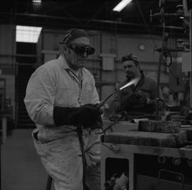 Welding, 1968; man wearing protective goggles and gloves holding a welding torch ; man working in...