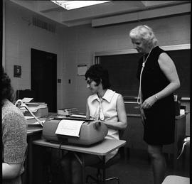 BC Vocational School Commercial Program; student typing ; instructor looking at student's typewri...
