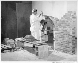 Bricklaying; Student building the arch on a brick fireplace in a workshop, cement and other build...