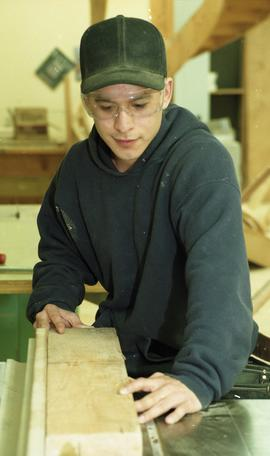 Male First Nations student wearing safety goggles and maneuvering a piece of wood [4 of 5 photogr...