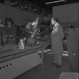 Sheet metal, 1968; instructor watching a student using a hammer to shape a piece of metal ; stude...