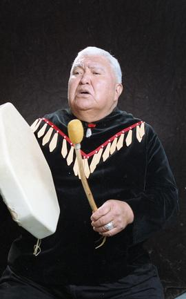 Bob George, First Nations elder, in First Nations garment playing an instrument [29 of 36 photogr...