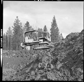 Heavy duty equipment operator, Nanaimo ; man operating a bulldozer on a hill of dirt ; forest in ...