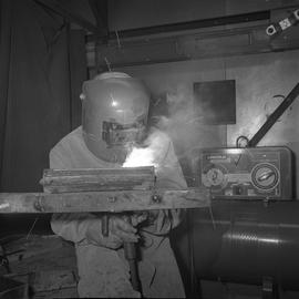 Welding, Terrace, 1968; person wearing a face shield welding, a Lincoln welder in background