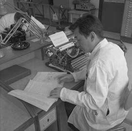 Office Machine Mechanic, 1968; man reading a typewriter repair manual, typewriter on desk in fron...
