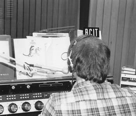 Broadcast Communications; man wearing headphones working in a radio control booth (white border c...
