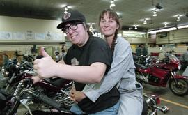 BCIT women in trades; power equipment, two people sitting on motorbikes inside a shop [1 of 3 pho...