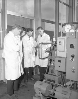 Mechanical technology, 1967; four men in lab coats looking at machinery