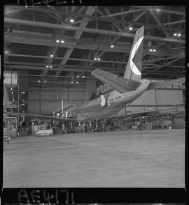 BC Vocational School; Aeronautics instructor and students working on the wings of a jet airliner ...