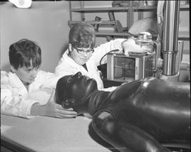 Medical radiography, 1968; woman in a lab coat positioning a manikin for an x-ray, woman in a lab...