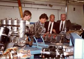 Small crowd looking at airplane engine parts