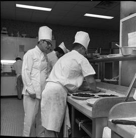 BC Vocational School Cook Training Course ; instructor (Arthur L. Brown) talking to a student who...