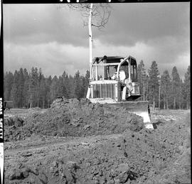 Heavy duty equipment operator, Nanaimo ; man operating a bulldozer moving dirt ; forest in backgr...