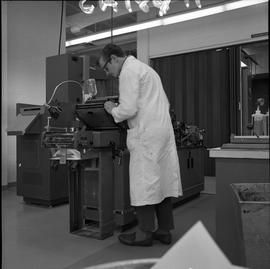 BCVS Graphic arts ; a man adjusting printing equipment ; printing equipment and tools in background