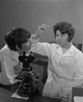 Medical Lab; two women in lab coats examining liquid in a test tube ; test tubes and a microscope...
