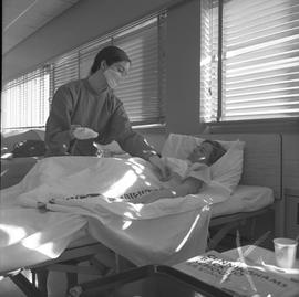 Practical nursing, Prince George, 1968; nurse wearing a face mask attending to a patient [2 of 3]