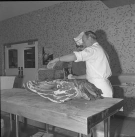 Meat cutting, 1968;  instructor holding a saw on a large piece of meat and a student watching