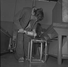 Sheet metal, 1968; student using a tool to shape a piece of metal ; students working in background