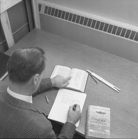Stationary engineering, 1968; man sitting at a desk taking notes from an engineering textbook