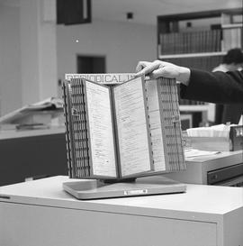 BCIT Library ; person flipping through a periodical index