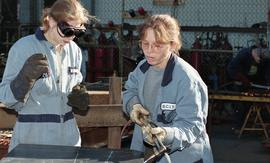 BCIT women in trades; ironworks, students in coveralls wearing safety goggles while using ironwor...
