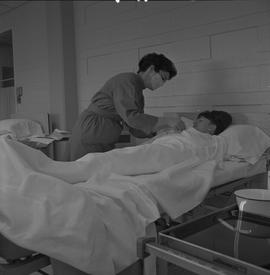 Practical nursing, Prince George, 1968; nurse wearing a face mask taking a patient's temperature