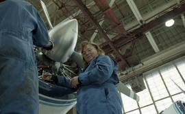 Canadian women at work; woman in uniform working on a jet engine with tools inside a hangar [1 of...